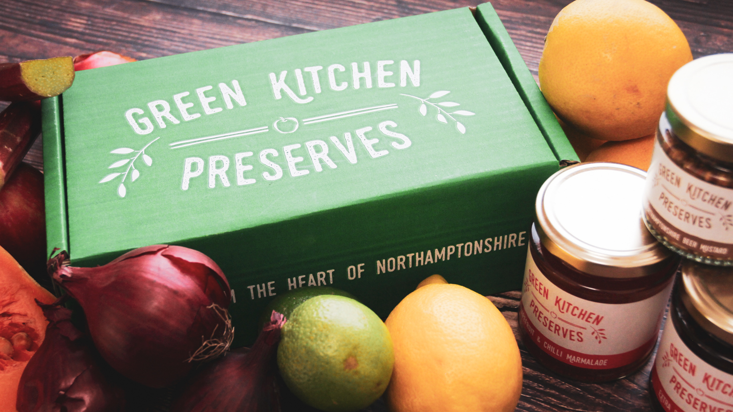 a green kitchen preserves gift box of jars containing jams, chutneys and marmalades on a wooden background with fruit and vegetables on a wooden background