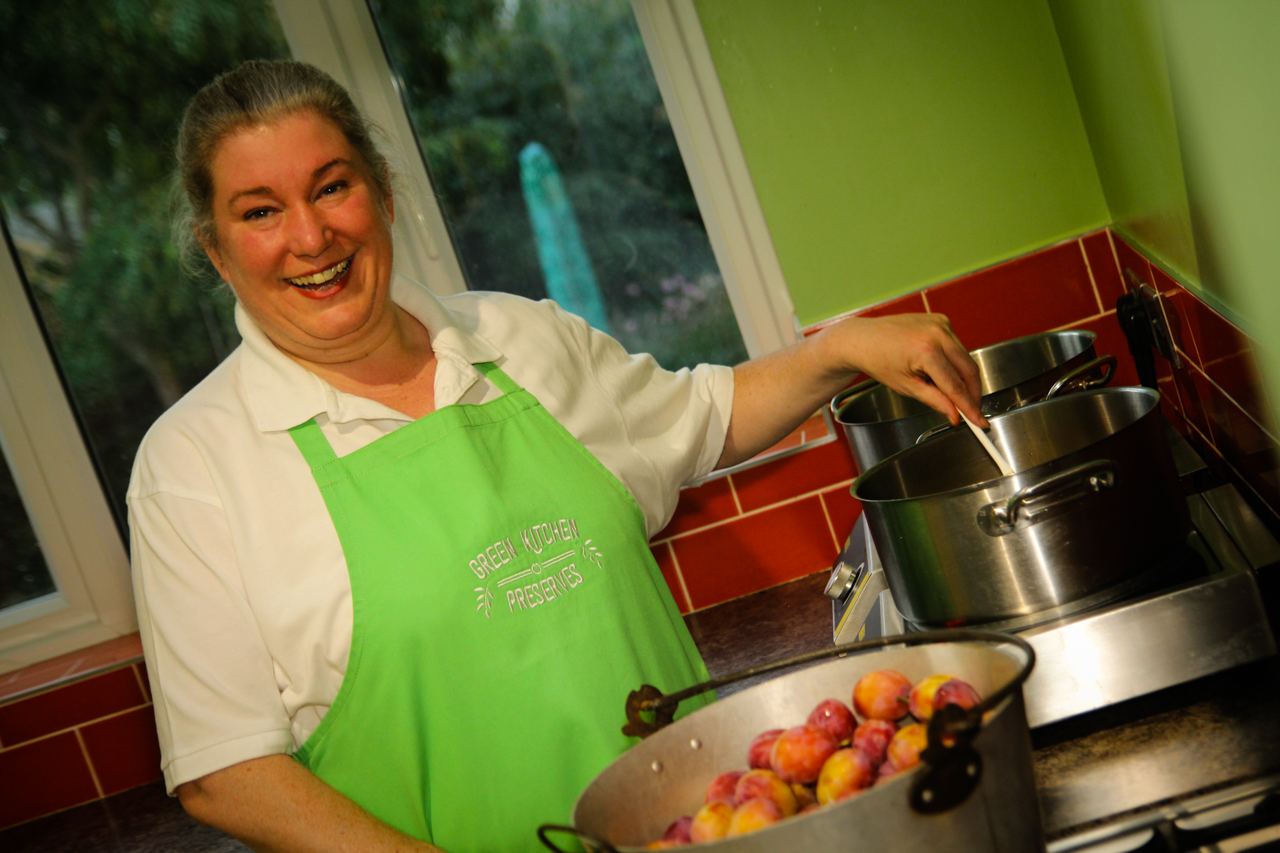 a photo of alison cox in the green kitchen preserves kitchen stirring chutney in a pot