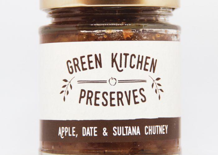 a jar of apple, date & sultana chutney on a white background