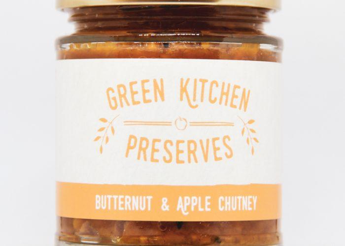 a jar of butternut & apple chutney on a white background