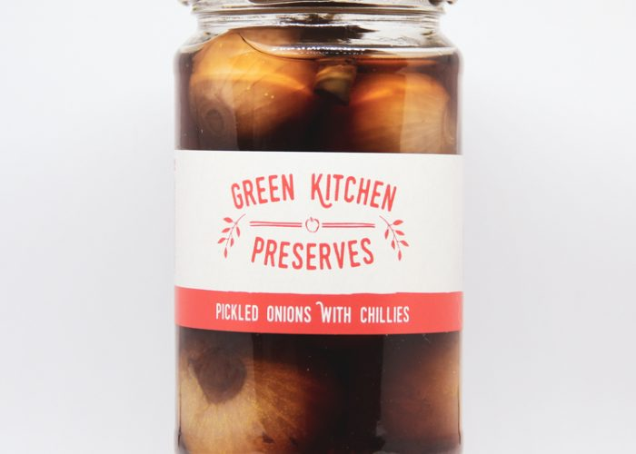 a large jar of spicy pickled onions with chillies on a white background