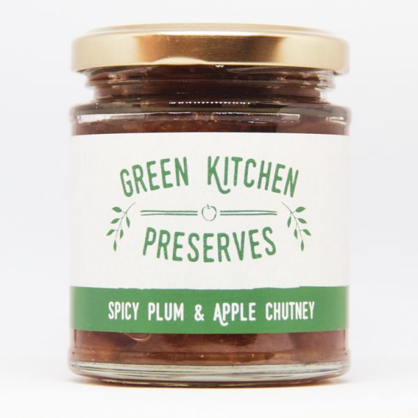 a jar of spicy plum & apple chutney on a white background
