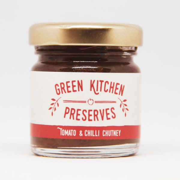 a small jar of tomato & chilli chutney on a white background