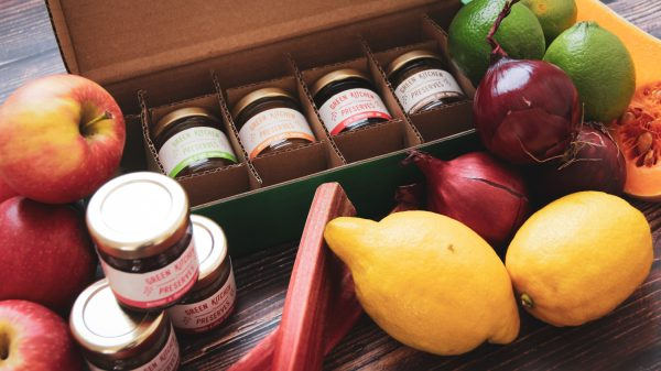 an assorted box of mini jars of chutneys, jams and marmalades on a wooden background with fruit and vegetables around it
