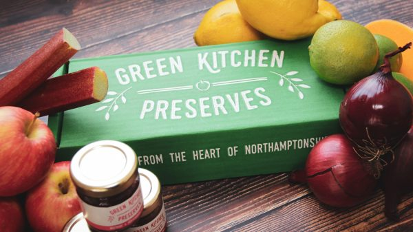 a green kitchen preserves gift box of mini jars containing jams, chutneys and marmalades on a wooden background with fruit and vegetables on a wooden background