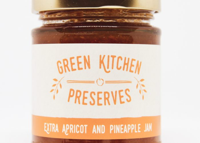 a jar of apricot & pineapple jam on a white background