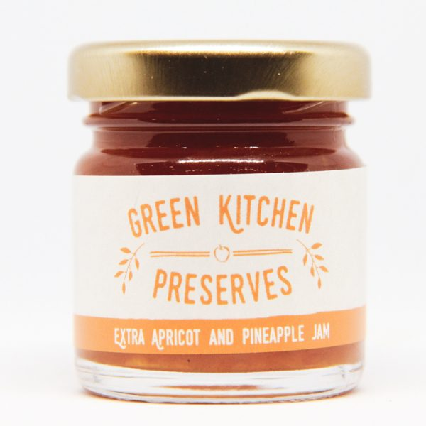 a mini jar of apricot & pineapple jam on a white background